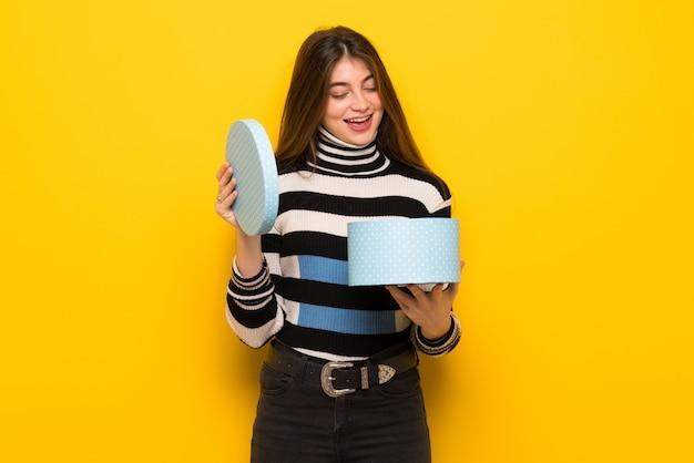 Jovem mulher na parede amarela, segurando a caixa de presente nas mãos