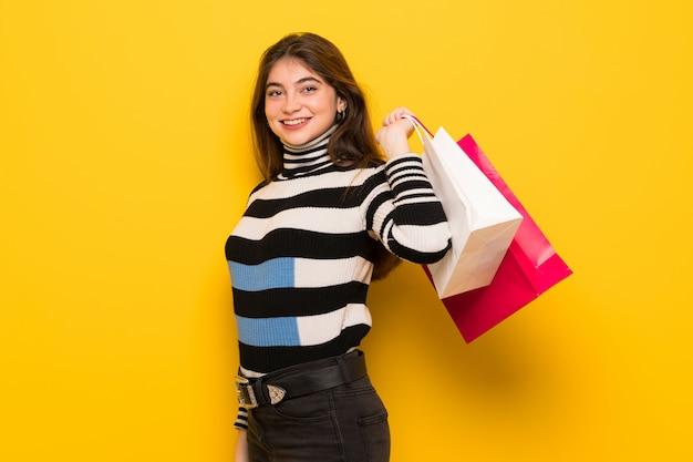 Jovem mulher na parede amarela segurando um monte de sacolas de compras