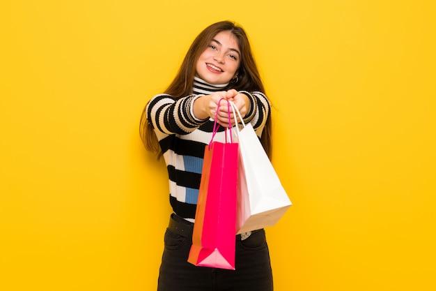 Jovem mulher na parede amarela segurando um monte de sacos de compras
