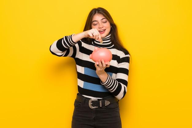 Jovem mulher na parede amarela tomando um cofrinho e feliz porque está cheio
