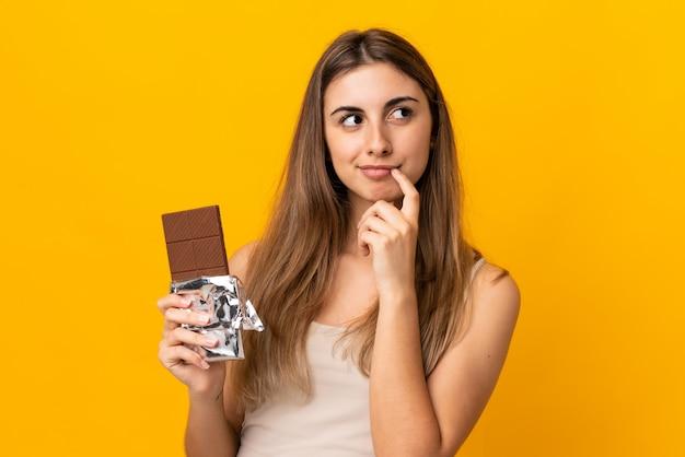 Jovem mulher na parede amarela, tomando uma tablete de chocolate e tendo dúvidas