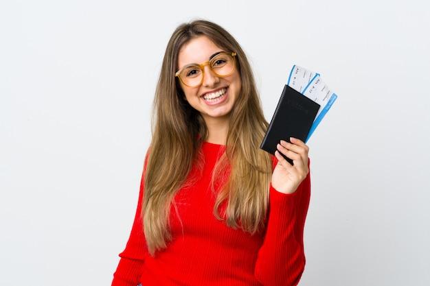 Jovem mulher na parede branca feliz em férias com bilhetes de avião e passaporte