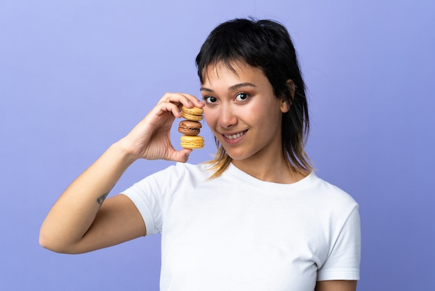 Jovem mulher na parede roxa segurando macarons franceses coloridos e sorrindo muito