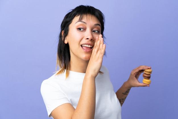 Jovem mulher na parede roxa segurando macarons franceses coloridos e sussurrando algo