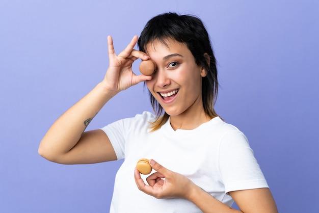Jovem mulher na parede roxa segurando macarons franceses coloridos