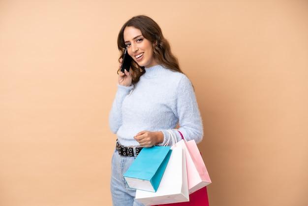 Jovem mulher na parede segurando sacolas de compras e chamando um amigo com seu telefone celular