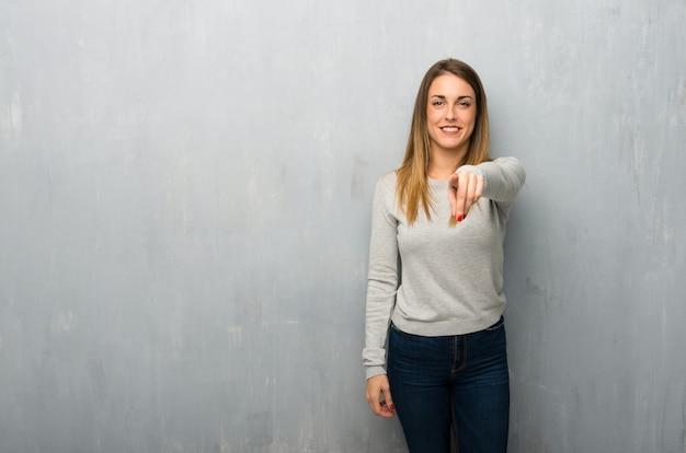 Jovem mulher na parede texturizada aponta o dedo para você com uma expressão confiante
