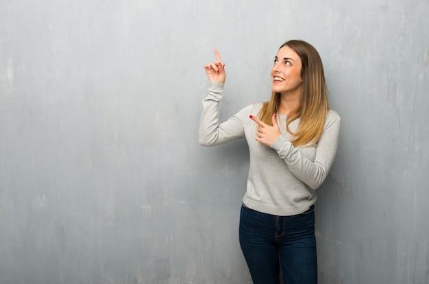 Jovem mulher na parede texturizada, apontando com o dedo indicador e olhando para cima