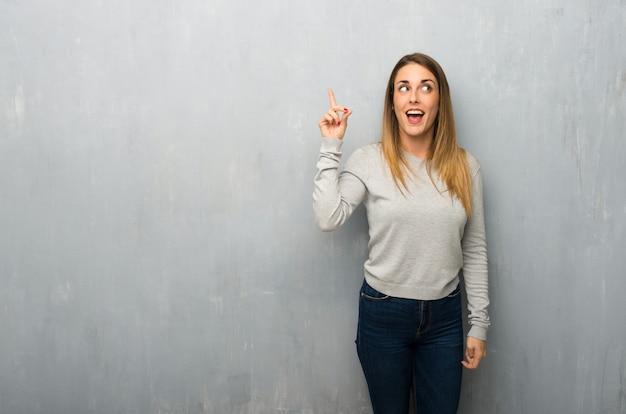Jovem mulher na parede texturizada com a intenção de perceber a solução ao levantar um dedo