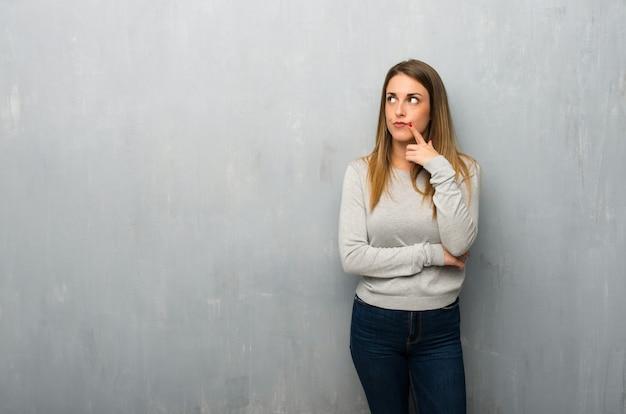 Jovem mulher na parede texturizada com dúvidas enquanto olhando para cima