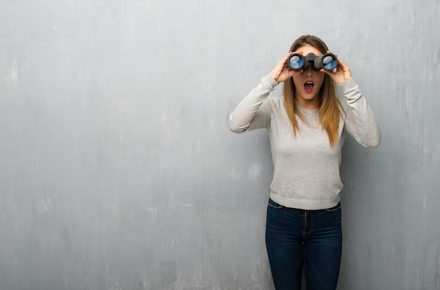Jovem mulher na parede texturizada e olhando à distância com binóculos