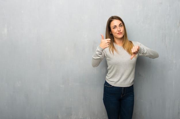 Jovem mulher na parede texturizada fazendo bom sinal ruim. indeciso entre sim ou não