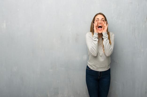 Jovem mulher na parede texturizada gritando e anunciando algo