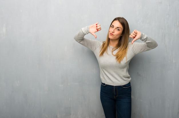 Jovem mulher na parede texturizada, mostrando o polegar para baixo com ambas as mãos