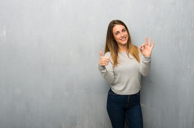 Jovem mulher na parede texturizada, mostrando sinal de ok e dando um polegar para cima gesto