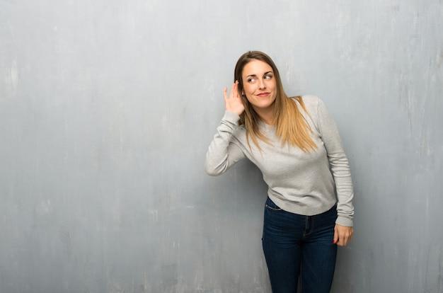 Jovem mulher na parede texturizada ouvir algo, colocando a mão sobre a orelha