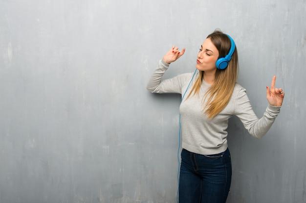 Jovem mulher na parede texturizada ouvir música com fones de ouvido e dançar