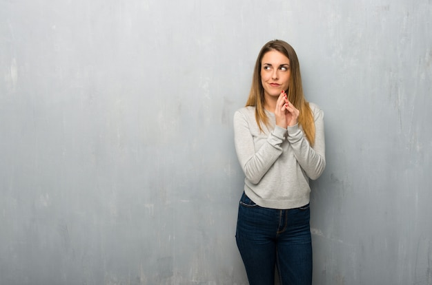 Jovem mulher na parede texturizada planejando algo