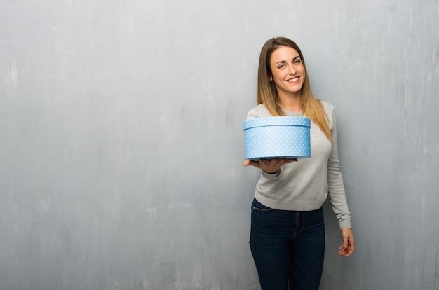 Jovem mulher na parede texturizada segurando um presente nas mãos