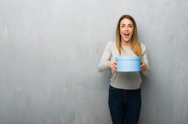 Jovem mulher na parede texturizada surpreendeu porque foi dado um presente