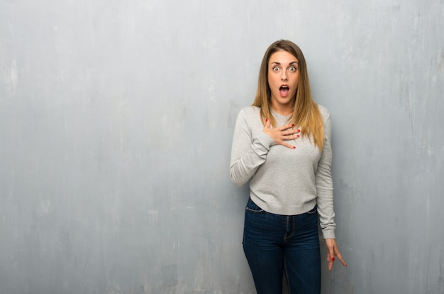 Jovem mulher na parede texturizada, surpreso e chocado ao olhar para a direita