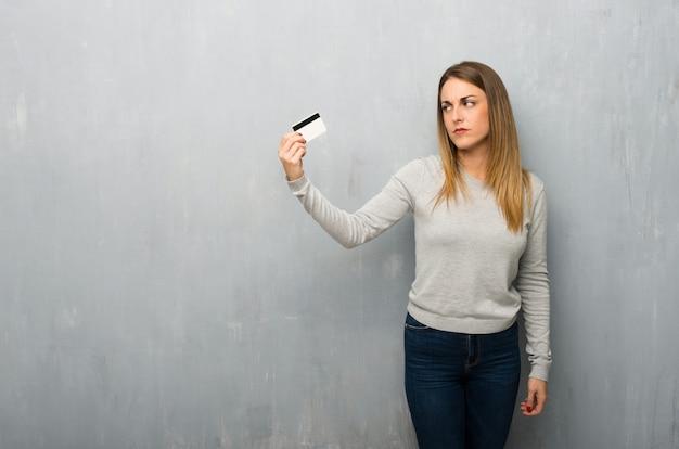 Jovem mulher na parede texturizada, tendo um cartão de crédito sem dinheiro