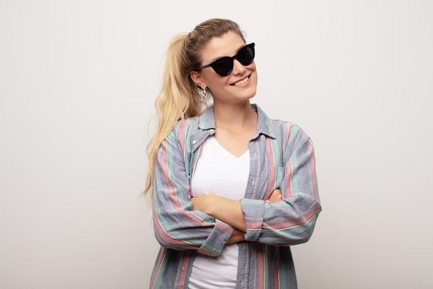 Jovem mulher na parede usando óculos de sol