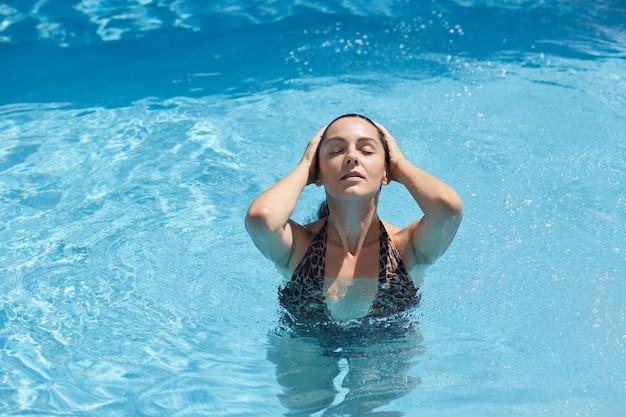Jovem mulher na piscina, tocando seus cabelos molhados e mantendo os olhos fechados, senhora em elegante maiô posando na água azul, relaxante no spa resort.