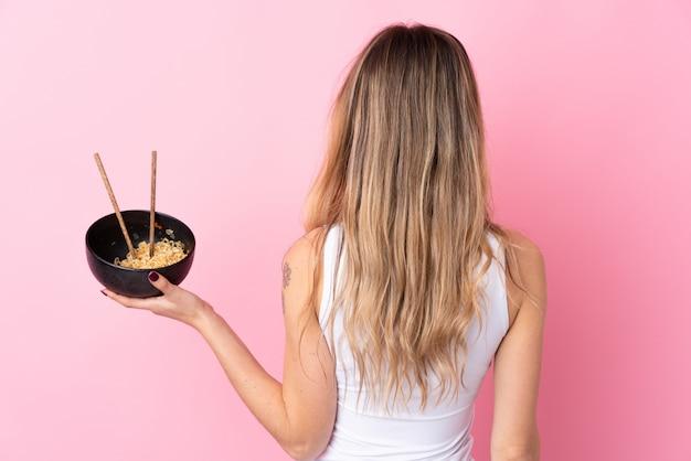 Jovem mulher na posição traseira, segurando uma tigela de macarrão com pauzinhos