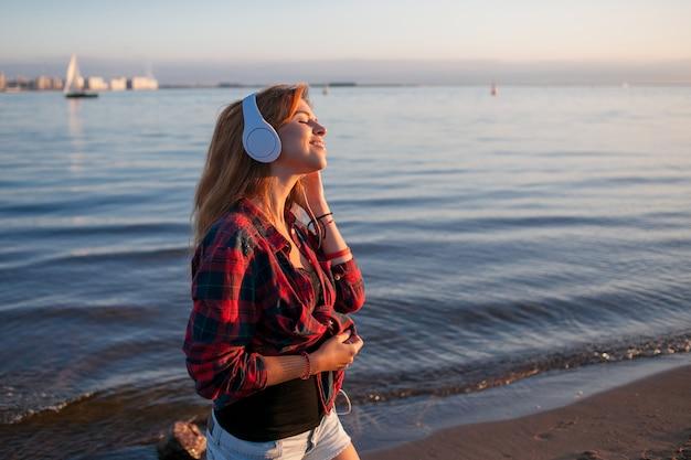 Jovem mulher na praia ouvindo música