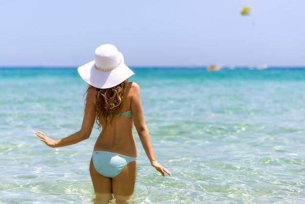 Jovem mulher na praia. retrato de uma menina com chapéu branco se divertindo na água