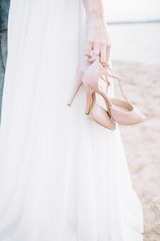 Jovem mulher na praia segurando sapatos de salto alto.