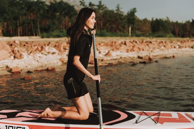 Jovem mulher na ressaca do remoço do roupa de mergulho com pá.