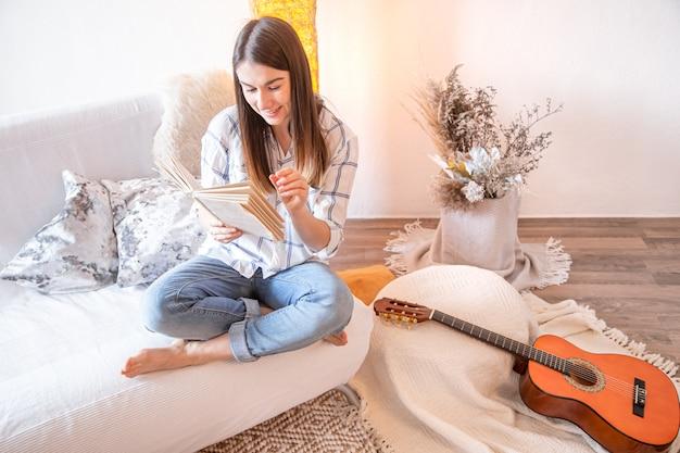 Jovem mulher na sala de estar com um violão.