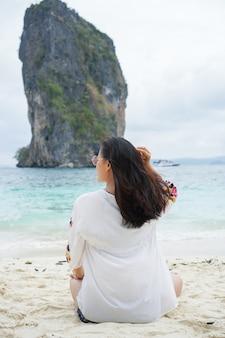 Jovem mulher na sessão feliz na areia. tour itinerante na ásia: krabi, tailândia.