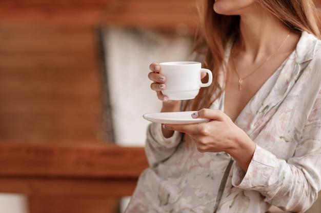 Jovem mulher na varanda segurando uma xícara de café ou chá de manhã.