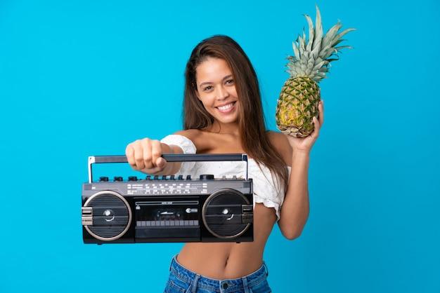 Jovem mulher nas férias de verão, segurando um rádio e um abacaxi