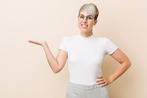 Jovem mulher natural autêntica, vestindo uma camisa branca mostrando algo na palma da mão e segurando a outra mão na cintura