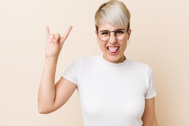 Jovem mulher natural autêntica, vestindo uma camisa branca, mostrando um gesto de chifres