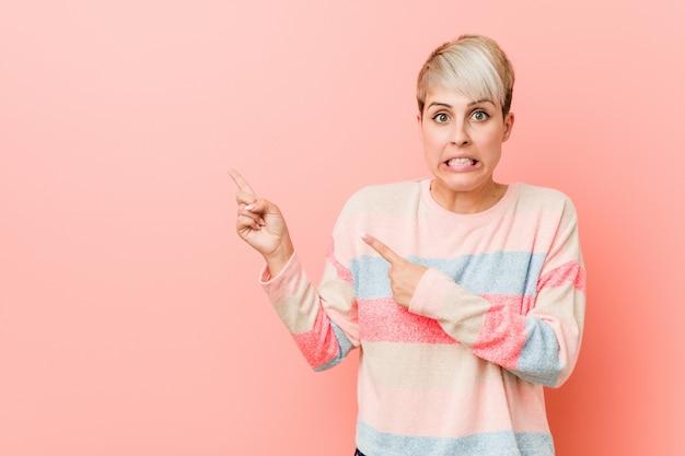 Jovem mulher natural chocou apontando com o dedo indicador para um espaço em branco.