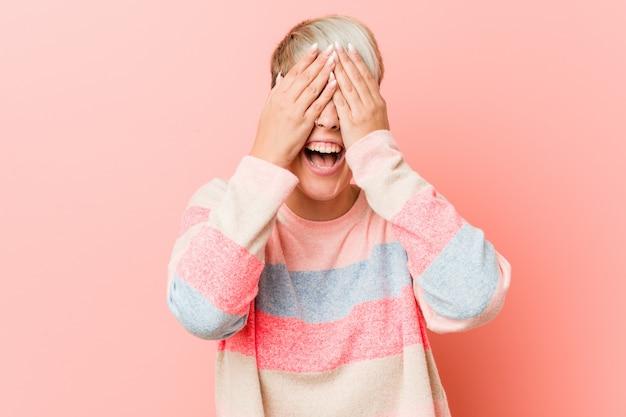 Jovem mulher natural cobre os olhos com as mãos, sorri amplamente esperando por uma surpresa.