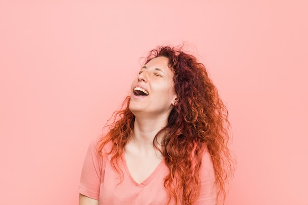 Jovem mulher natural e autêntica ruiva relaxada e feliz rindo, pescoço esticada, mostrando os dentes.