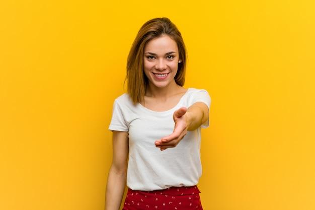 Jovem mulher natural, esticando a mão na câmera em cumprimentar o gesto