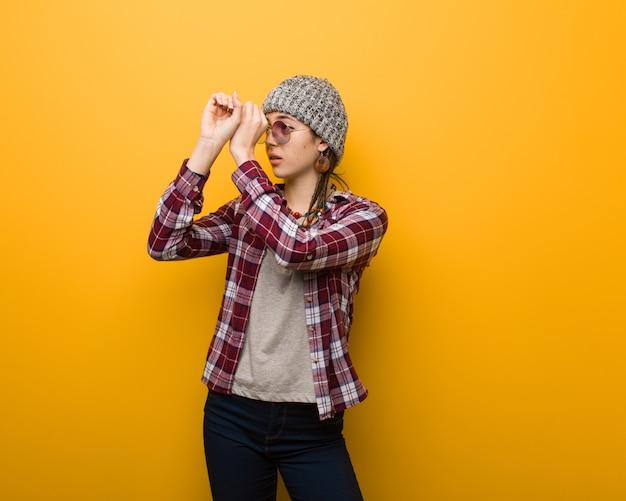 Jovem mulher natural hippie fazendo o gesto de uma luneta