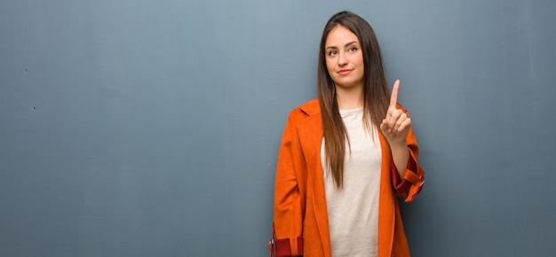 Jovem mulher natural mostrando o número um