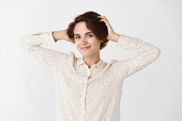 Jovem mulher natural sem maquiagem, sentindo-se despreocupada e relaxada, tocando o cabelo e sorrindo, em pé na parede branca