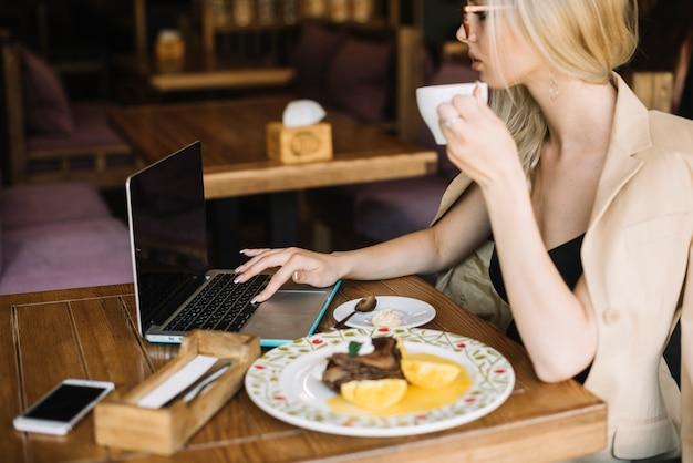 Jovem mulher navegação portátil enquanto tomando café da manhã no café