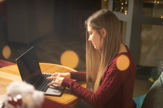 Jovem mulher navegando na internet no café à noite