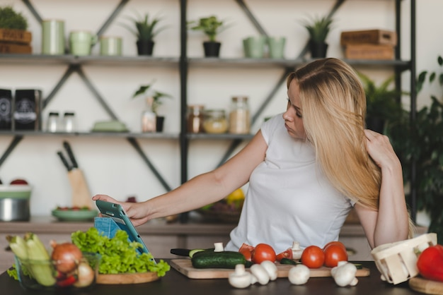 Jovem mulher navegando na tabuleta digital com muitos vegetais no balcão da cozinha