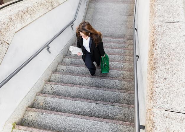 Jovem, mulher negócio, com, jornal, e, saco, andar escadas